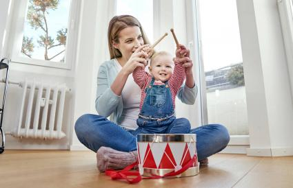 Mother and baby girl playing drums