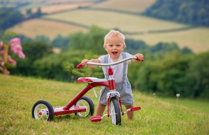 toddler child playing with tricycle