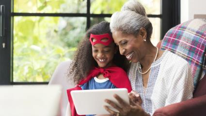 Smiling grandmother and granddaughter using tablet
