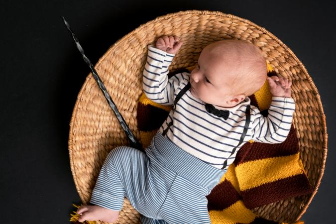 Little newborn baby boy with a magic wand, black background and scarf
