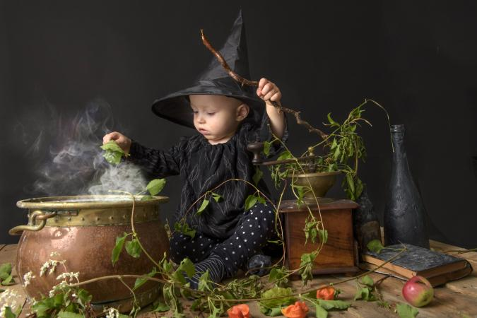 Little baby witch cooking a potion