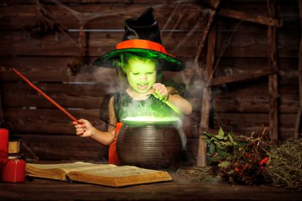 Little witch child cooking potion in cauldron with spell book