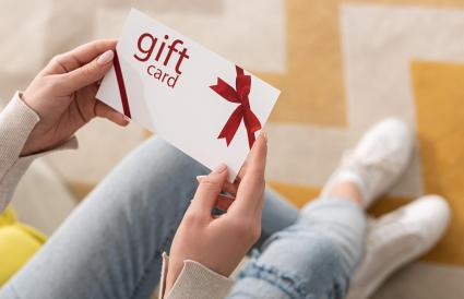 girl holding gift card