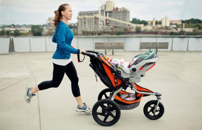 Woman pushing baby stroller while jogging