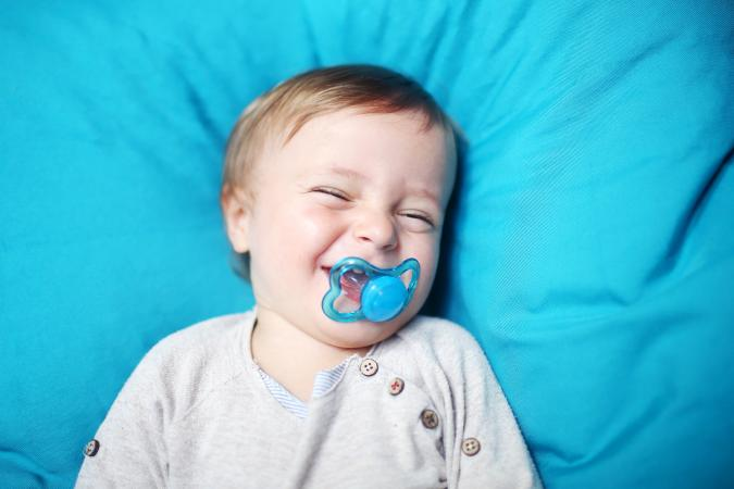 Toddler boy with pacifier surrounded by blue