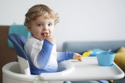 A 15 months old boy eating in his high chair