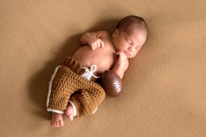 Newborn baby wearing football uniform