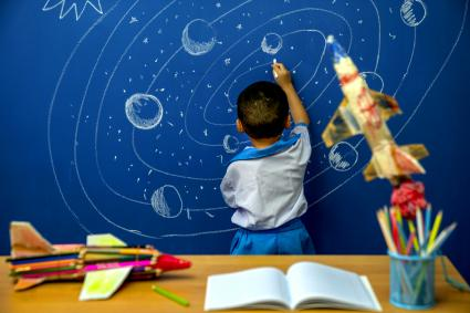 Little boy reaching for rocket in drawn space