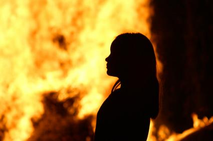 Silhouette of Girl Standing Against Fire At Night
