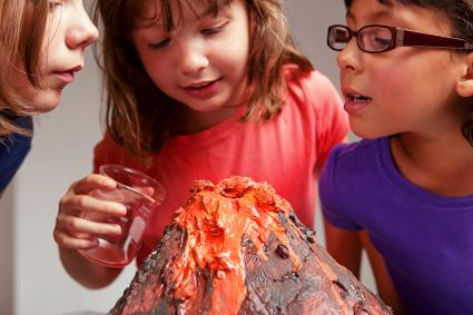 Little girls make their volcano science project erupt