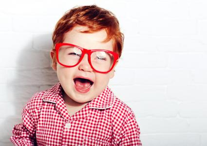 Portrait of cute laughing toddler boy in glasses