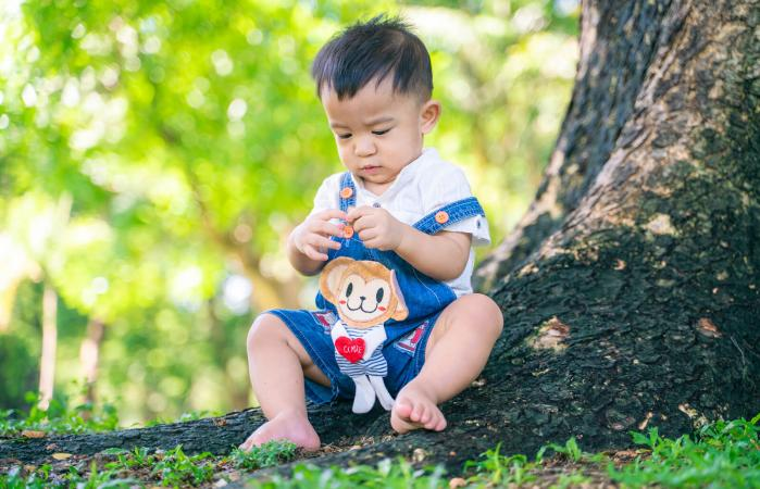baby boy sitting by tree
