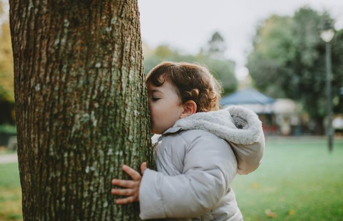 baby girl kissing tree trunk