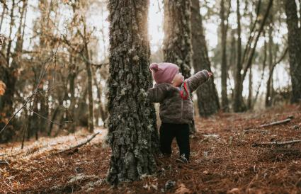 Baby girl standing in forest