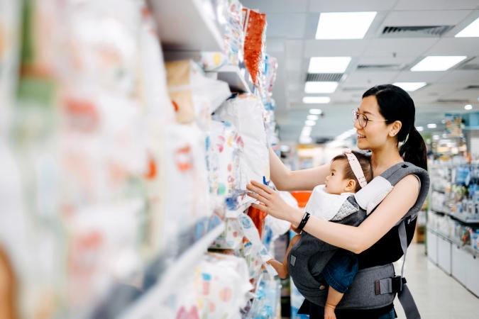 Young mother carrying cute baby girl shopping for diapers
