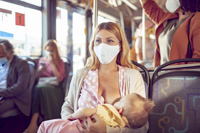 Mother breastfeeding her baby while commuting on a bus