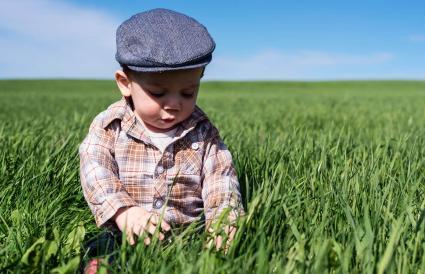 boy enjoys sitting in tall grass