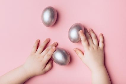 Children's hands and silver eggs on a pink background