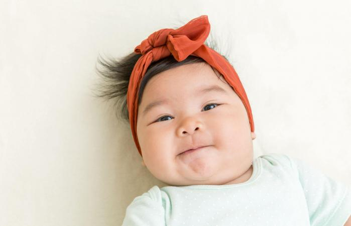 baby smiling on the bed