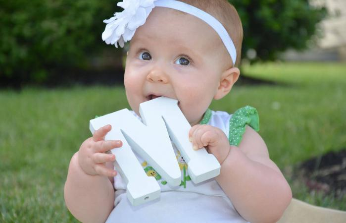 Cute baby girl with wooden M