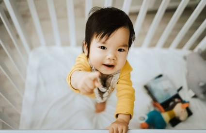 baby girl standing in her crib