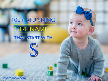 Baby girl crawling among letter blocks