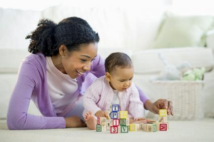 Woman playing with blocks with baby girl