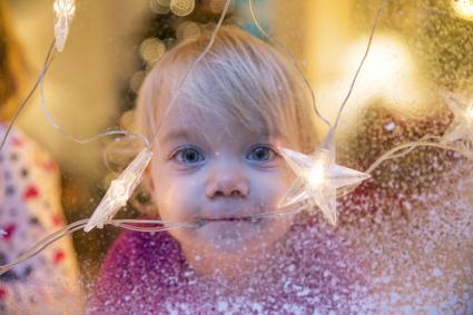 Baby girl looking out of window with Christmas star