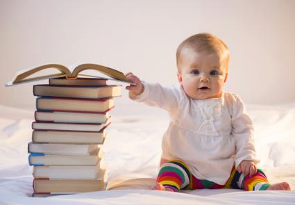 Baby sitting in bed with stack of books
