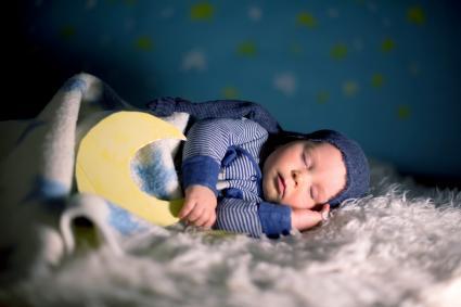 Little baby boy with cute teddy bear and moon