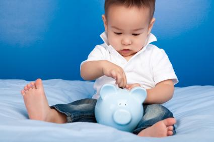 Boy putting money in blue piggy bank