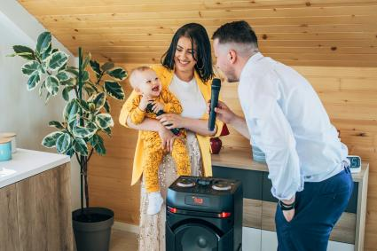 Happy family with their baby son, singing and dancing at home