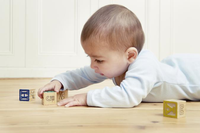 Baby lying on front playing with building blocks