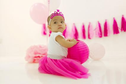 Cute Baby Girl In Dress With Party Decoration