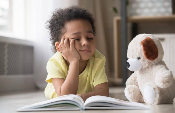Bored little boy reading book