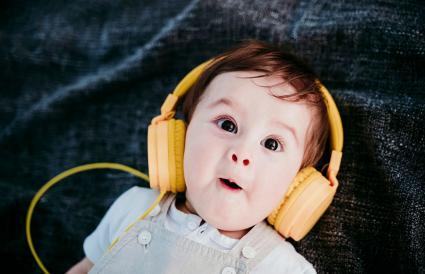 Cute baby boy wearing headphones