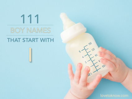 Infant hands holding bottle of milk on light blue floor background