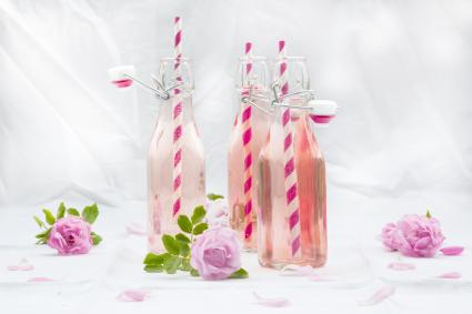 Rose punch in bottles with decorative pink and white straws