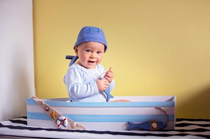Cute toddler boy, sitting in a big wooden boat at home