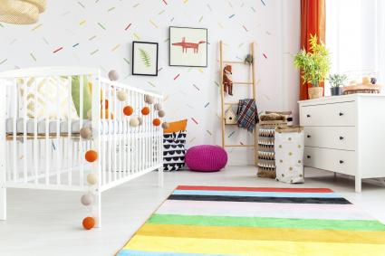 White wooden cradle with colorful balls in modern baby room