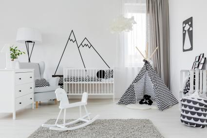 Child room with white furniture, carpet, tent and mountain wall sticker