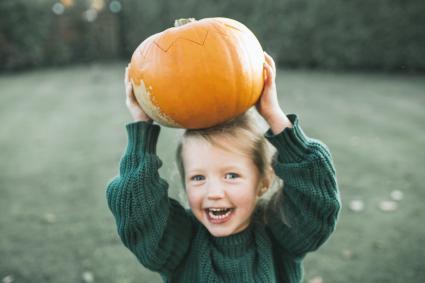Child holding a pumpkin