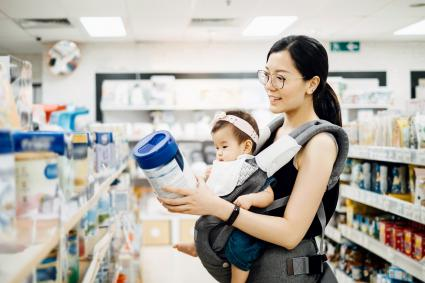 Mother carrying baby girl and looking at a variety of baby formula