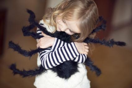 Girl hugging large toy spider