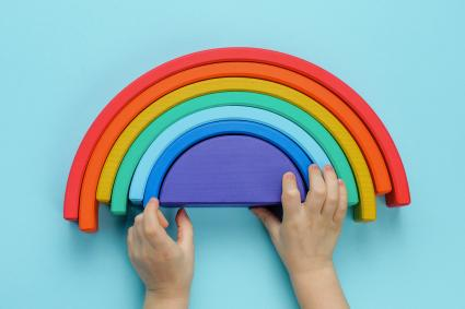 Kids hands playing with wooden toy rainbow