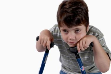 Image of a disabled young boy using crutches