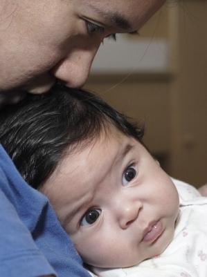 Dad holding dark-haired baby boy