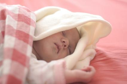 Infant sleeping in pink bedding