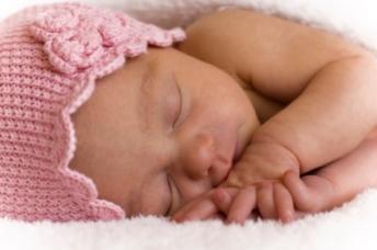 Infant wearing a pink bonnet
