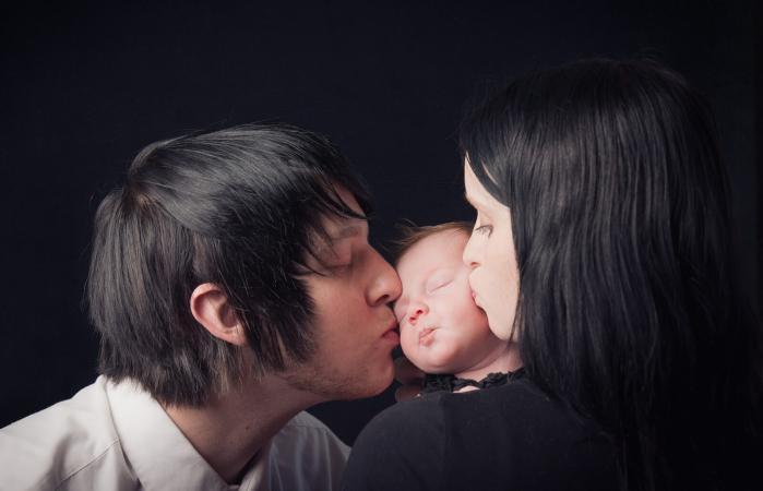 Padres góticos besando a su hijo recién nacido